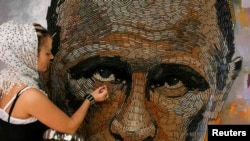 Ukrainian artist Daria Marchenko works on a portrait of Russian President Vladimir Putin that is made out of 5,000 cartridges brought from the frontline in eastern Ukraine.