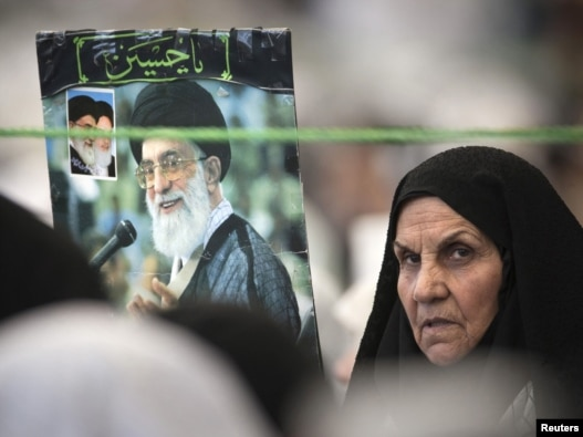 A woman holds a picture of Supreme Leader Ayatollah Ali Khamenei while attending Friday Prayers at Tehran University, which hosted the National Soft War Forum.