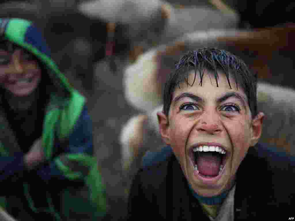A boy reacts with a laugh as he waits for customers at an animal market on a rainy day on the outskirts of Kabul. - Photo by AFP