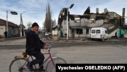 An elderly man cycles past a burnt-out building in the majority-Dungan village of Masanchi in southern Kazakhstan's Zhambyl region, close to the border with Kyrgyzstan, on February 12.