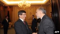 Iranian Foreign Minister Ali Akbar Salehi (right) greets his Turkish counterpart Ahmet Davutoglu.