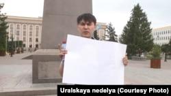 Ешқандай жазу я сурет жоқ ақ плакат ұстаған азаматтық белсенді Аслан Сагутдинов орталық алаңда тұр. Орал, 6 мамыр 2019 жыл.