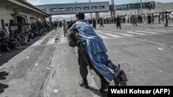 Мужчина несет на себе раненого и направляется к толпе людей, ожидающих очередной борт в кабульском аэропорту. 16 августа 2021 года