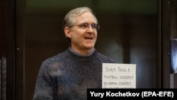 Paul Whelan holds up a sign denouncing the legal proceedings against him as he stands inside the defendant's cage during a court hearing in Moscow on June 15.