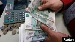 Сотрудник компании пересчитывает российские рубли. 6 ноября 2014 года.