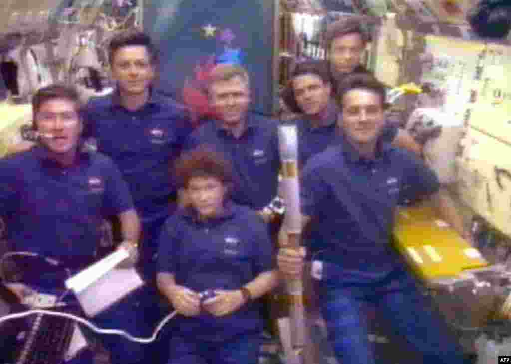 "Space shuttle ""Columbia"" crew member Richard Linnehan (right) holds the Olympic torch in July 1996, the first relay tour into space."