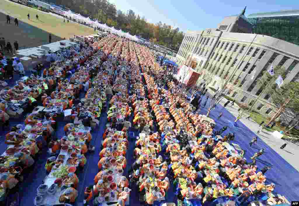 Some 2,000 South Korean volunteers make 140 tons of kimchi, a traditional Korean dish of spicy fermented cabbage and radish, in a park in Seoul. City officials will hand out kimchi to about 14,000 poor households in an event marking the start of the winter season. (AFP/Jung Yeon-Je)