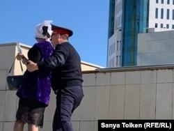 Полиция қызметкері Қанағат Тәкееваны президент әкімшілігі кеңсесіне қарай жетектеп барады. Нұр-Сұлтан, 20 қыркүйек 2019 жыл.