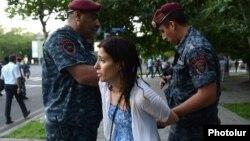 Полицейские подвергают приводу в полицию одну из участниц акции протеста утром 23 июня