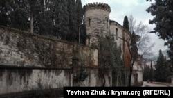Круглая башня с узкими окнами в стиле бойниц похожа на оборонительную