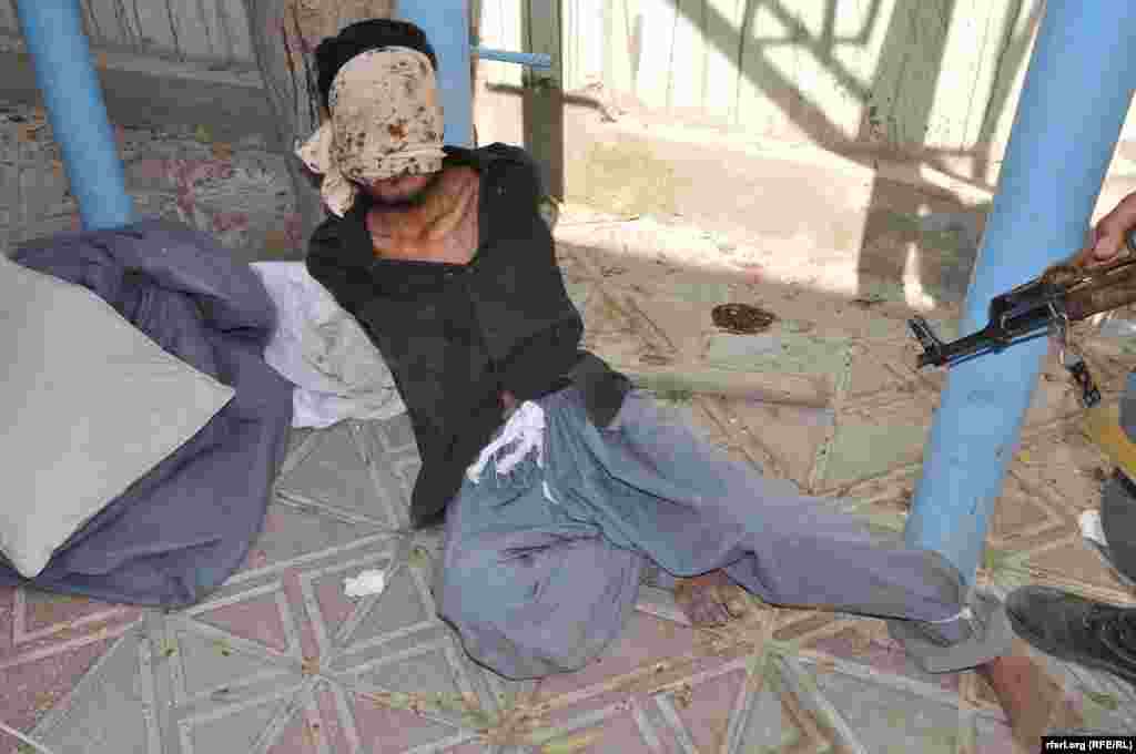 A suspected militant being held by Afghan security forces in Kunduz.