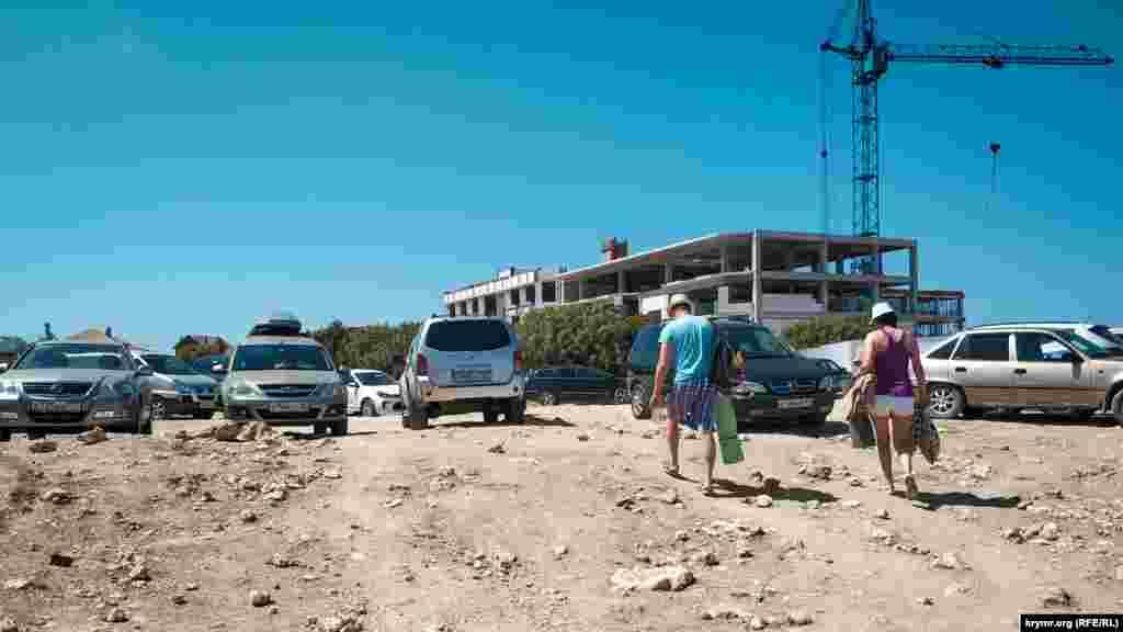 Парковки возле пляжа нет, машины оставляют на грунтовой площадке, разбитой грузовиками