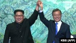 Солтүстік Корея басшысы Ким Чен Ын (сол жақта) мен Оңтүстік Корея президенті Мун Чжэ Ин саммит аяқталатын сәтте бірге қол көтеріп тұр. Шекараға жақын жақын Пханмунджом елді мекені, 27 сәуір 2018 жыл.
