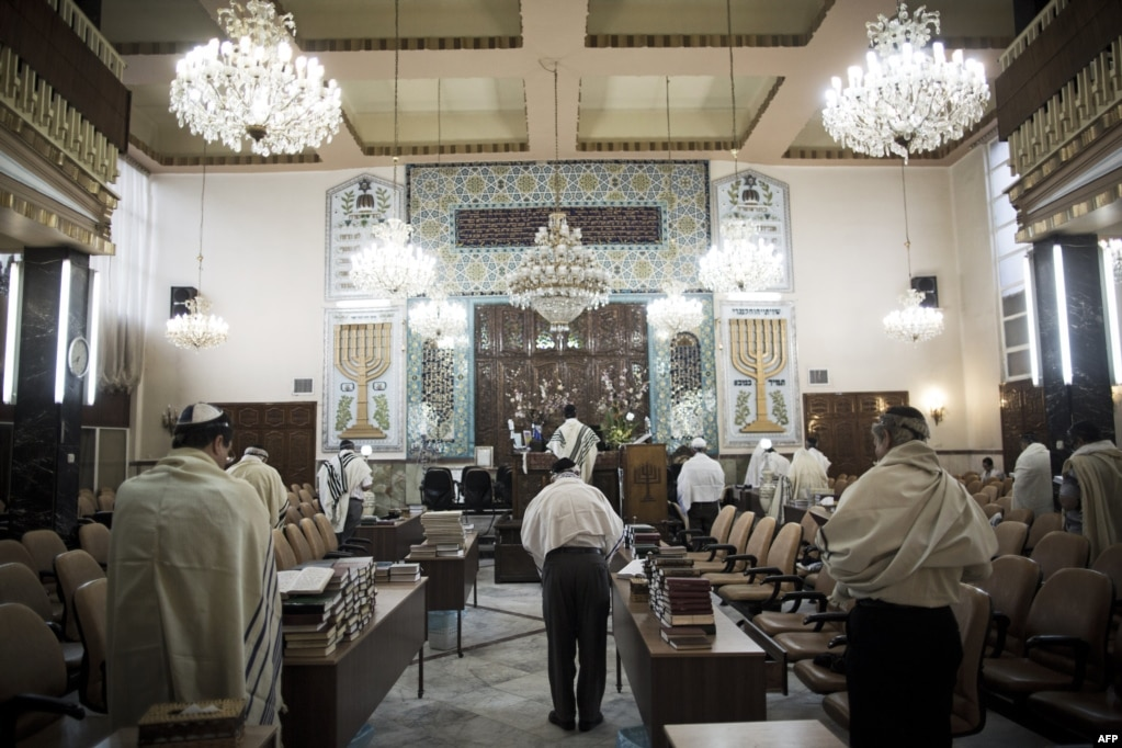 Iranian Jewish men wearing Tallit shawls read from the Torah during morning prayers.
