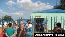 Родственники задержанных стоят у ворот Кенкиякского поселкового отделения полиции. Поселок Кенкияк Актюбинской области,1 июля 2011 года.