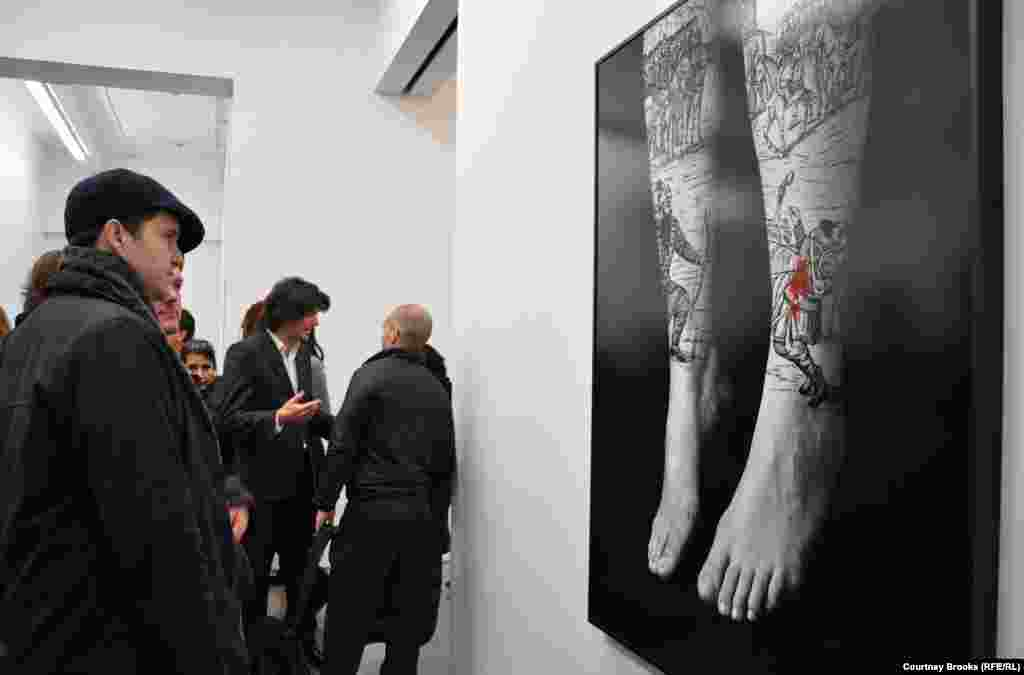 Two men look at a photograph of hanging feet covered with depictions of a battle scene at Shirin Neshat's exhibition.