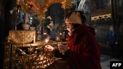 Верующая в защитной маске во Владимирском кафедральном соборе в Киеве с зажженной свечой у алтаря накануне православной Пасхи. 18 апреля 2020 года.