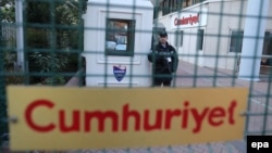 An armed private security officer stands guard in front of the headquarters of the Cumhuriyet daily newspaper in Istanbul.
