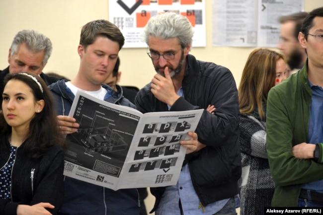 Американец Дэнис Кин (держит газету), создавший краеведческий сайт «Прогулки по Алматы», и его знакомый голландец, находящийся в городе проездом из Роттердама во Вьетнам, читают выпущенную командой ArchCode Almaty газету. Алматы, 31 марта 2017 года.