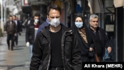 Pedestrians wearing protective masks against coronavirus (COVID-19) in Tehran, Iran. March 1, 2020.