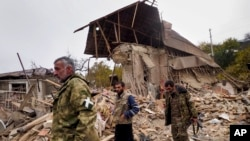Ethnic Armenian soldiers walk past a house destroyed by shelling by Azerbaijani artillery in Stepanakert, the main city of the breakaway region of Nagorno-Karabakh, on November 6.
