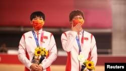 Велотректен олимпиада чемпионы атанған Бао Шаньцзюй мен Чжун Тяньши тұғырға елдің экс-басшысы Мао Цзедуннің төсбелгісін тағып шықты. Токио, 3 тамыз 2021 жыл.