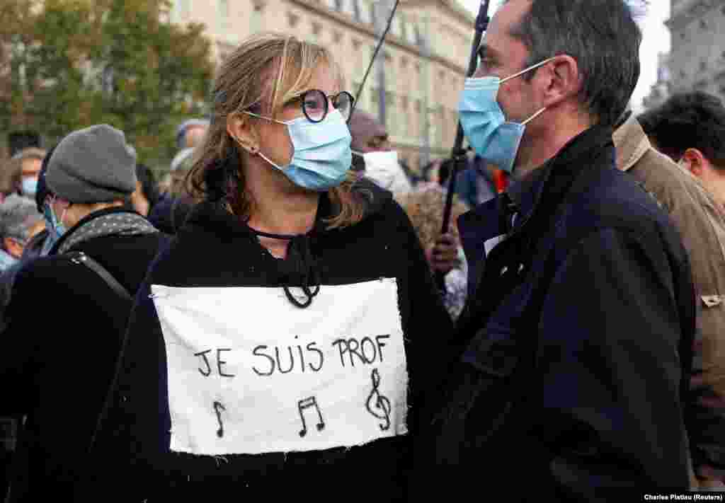 "People gather at the Place de la Republique in Paris, to pay tribute to Samuel Paty, the French teacher who was beheaded on the streets of the Paris suburb of Conflans-Sainte-Honorine, France, October 18, 2020. Placard reads ""I am a teacher""."