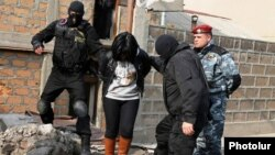 Armenia - Security forces detain a woman in a raid on a house in Yerevan's Nork district, 25Nov2015.