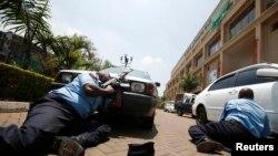 Pjesëtarët e policisë së Kenias fshihen prapa automobilave afër qendrës tregtare në kryeqytetin Najrobi