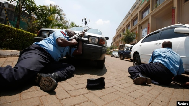 Kenyan police take cover outside the Westgate shopping center in Nairobi where gunmen from Somalia's Al-Qaeda-linked Al-Shabab movement went on a shooting spree on September 21.
