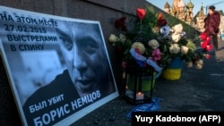 A woman passes by floral tributes at the site where opposition leader Boris Nemtsov was fatally shot on a bridge near the Kremlin in Moscow.
