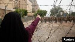 إمرأة مصرية موالية للرئيس المعزول محمد مرسي تؤشر صوب قوات احرس الجمهوري قرب مقرها في القاهرة