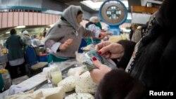 Покупательница у прилавка с молочной продукцией на рынке в Алматы.