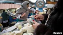 Покупатель у прилавка с молочной продукцией на Зеленом базаре в Алматы.