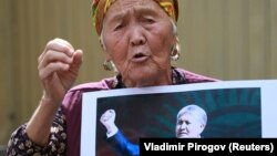 A supporter of Almazbek Atambaev attends a rally outside the State Committee for National Security in Bishkek on August 16.