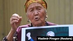 Gyrgyzystanyň öňki prezidenti Almazbek Atambaýewiň tarapdarlarynyp biri ýurduň Milli Howpsuzlyk boýunça döwlet komitetiniň binasynyň golaýynda çykyş edýär. 16-njy awgust, 2019 ý.