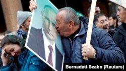 A supporter of Vladimir Putin kisses his portrait in Belgrade during the Russian president's visit to the Serbian capital on January 17.