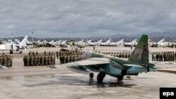 Российские и сирийские военнослужащие рядом с военными самолетами во время церемонии, посвященной выводу российских войск из Сирии. Авиабаза Хмеймим в Латакии, 15 марта 2016 года.