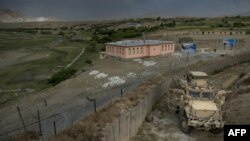 NATO forces use an armed vehicle to provide security while they rest at an Afghanistan National Army base between patrols near Bagram Airfield in 2014.