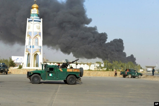 Afghan security forces arrive after a powerful explosion outside the provincial police headquarters in Kandahar Province last month. Talks have not led to any drop in Taliban attacks.