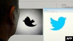 Компьютердегі Twitter белгісіне қарап отырған адам. (Көрнекі сурет)