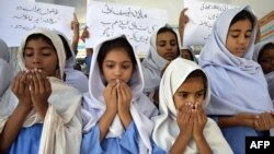 Schoolgirls pray for the recovery of gunshot victim Malala Yousafzai in Multan, in central Pakistan.