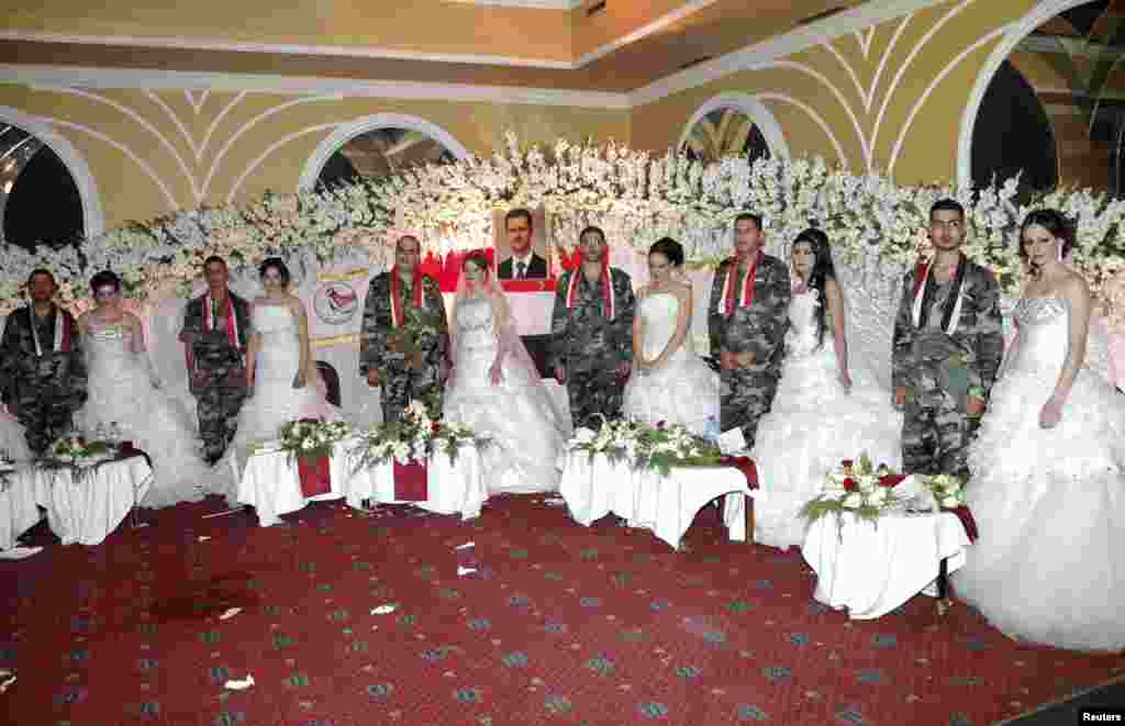 Soldiers loyal to Syrian President Bashar al-Assad pose for a photo with their brides during a mass wedding held in Homs city. (Reuters/SANA)