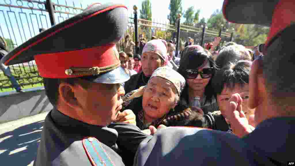 Supporters of detained Kyrgyz opposition lawmakers clash with police in front of the government headquarters in Bishkek. (AFP/Vyacheslav Oseledko)