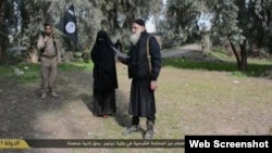 """Islamic State released this image showing a woman being stoned to death for adultery after being """"convicted"""" in a Shari'a court."""