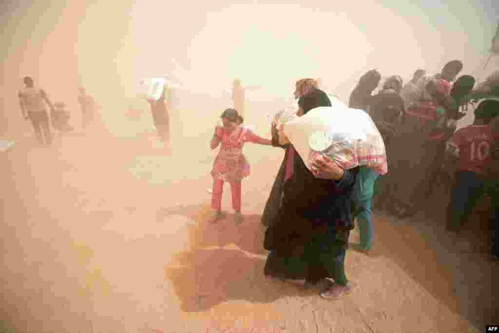 Displaced Iraqis who fled the government's operation against the Islamic State (IS) group in the city of Fallujah carry basic food items donated by an NGO called Preemptive Love Coalition amid a dust storm. (AFP/Haidar Muhammad Ali)