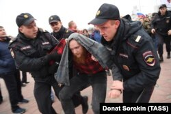 Police detain a man during an unauthorized rally in Yekaterinburg on October 7.