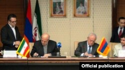 Iran - Energy Minister Hamid Chitchian (L) and his Armenian counterpart Yervand Zakharian sign a memorandum of understanding in Tehran, 16Dec2014.