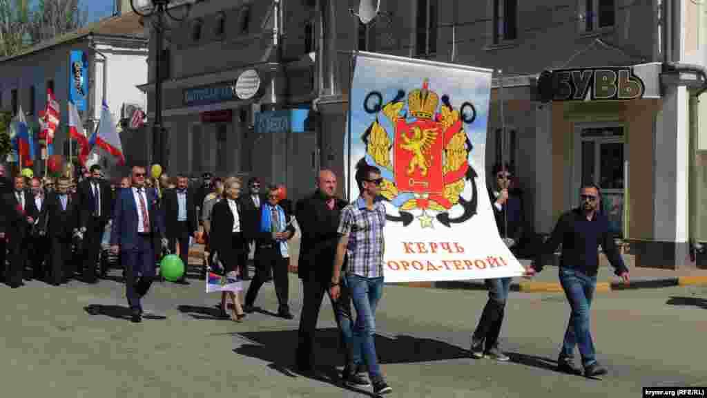 Во главе колонны несут плакат с гербом Керчи. За ним следуют представители подконтрольной Кремлю администрации города.