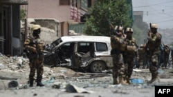 Afghan security forces stand guard near a damaged vehicle at the site of a suicide bombing that targeted NATO forces in Kabul on July 7.